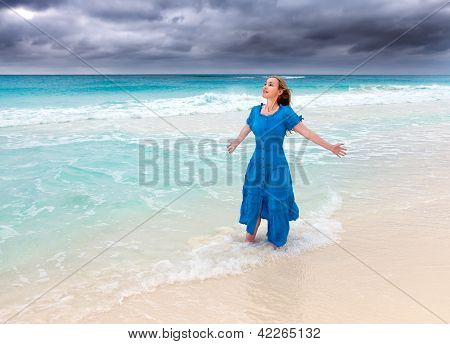 The woman in a long blue dress in a surf of stormy sea