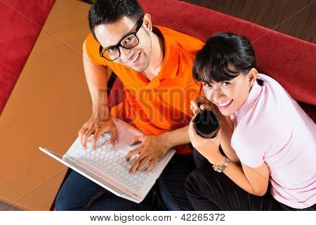 Indonesian couple sitting home on sofa with laptop using the internet for email and online shopping