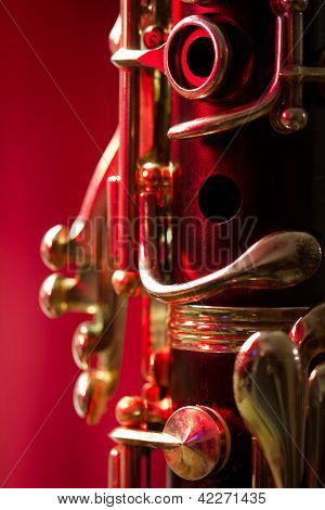 Close-up of a soprano clarinet with a red background