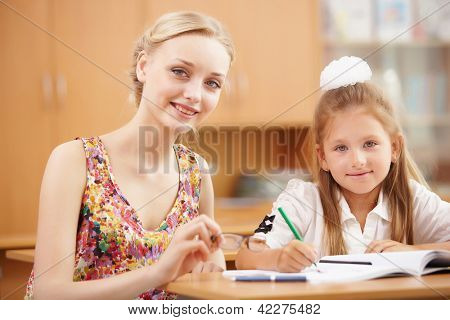 Young female teacher working with children at school