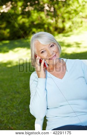 Senior woman making a phone call with her smartphone in a garden