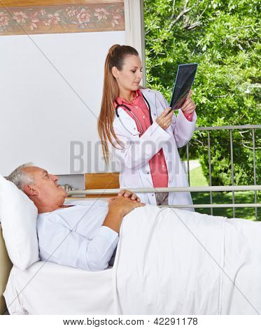 Radiologist looking at x-ray image with senior patient in a hospital