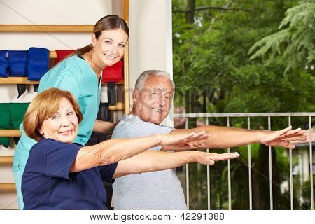 Happy physiotherapist with seniors doing fitness exercises for their backs