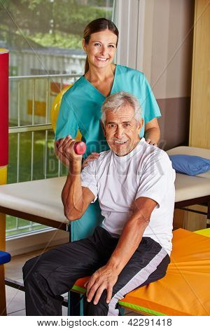 Senior man lifting dumbbells at remedial gymnastics with physiotherapist