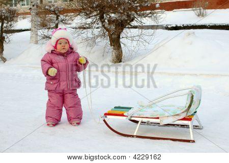 Pretty Little Girl In Winter Outerwear Near Sled (Sleigh).