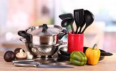 stock photo of saucepan  - composition of kitchen tools and vegetables on table in kitchen - JPG