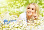 Image of pretty woman lying down on chamomile field, happy female holding in hand beautiful white fl