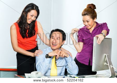 Asian colleague or manager or boss having  an office affair or flirting with two secretary or employees