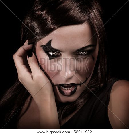 Scary portrait of young woman with aggressive makeup isolated on black background, terrifying witch, spooky vampire, Halloween party concept