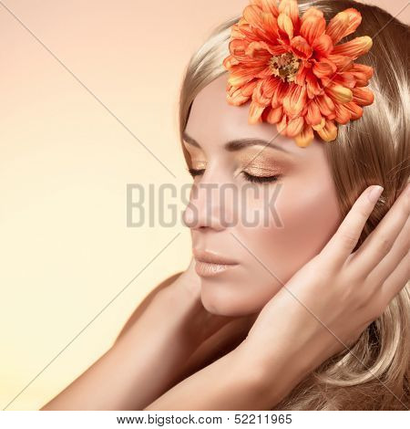 Gorgeous lady portrait isolated on beige background, closed eyes, big orange flower in head, stylish makeup, beauty salon concept