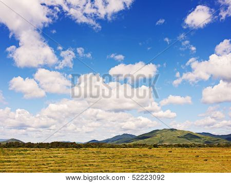 Landscape With Mountain Views, Arable Land, Blue Sky And Beautiful Clouds.