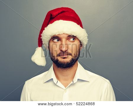 man in santa hat looking at something over grey background