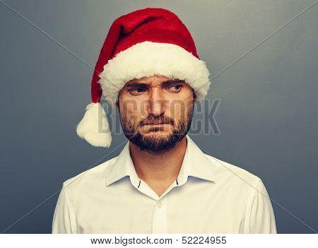 sad man in santa hat over dark background