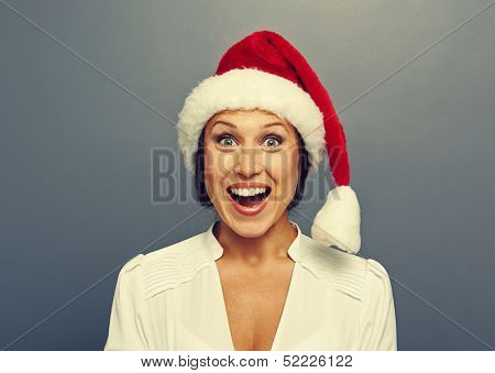 excited christmas woman in red hat over grey background