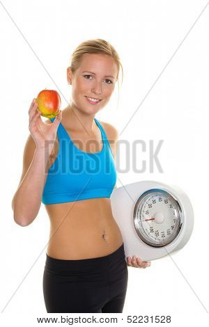a young woman with an apple and a scale. symbolic photo for and remove, as well as healthy eating