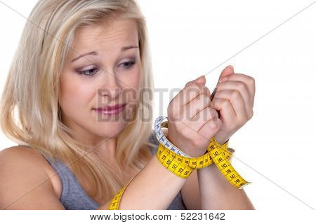 a young woman with a tape measure before the next diet. losing weight and fast