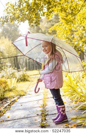 Slyly smiling girl posing under umbrella in park