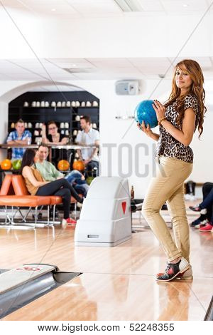 Side view portrait of young woman holding bowling ball with friends in background