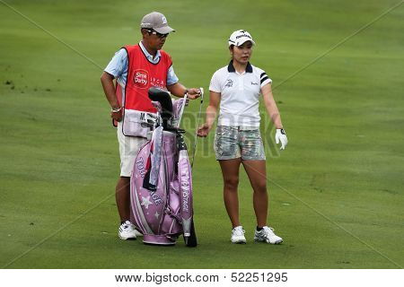 KUALA LUMPUR - OCTOBER 13: Mamiko Higa of Japan discusses with her caddy on the next play at the KLGCC course on the final day of the Sime Darby LPGA on October 13, 2013 in Kuala Lumpur, Malaysia.