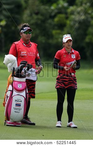 KUALA LUMPUR - OCTOBER 13: Pornanong Phatlum of Thailand speaks with her caddy on her next play at the KLGCC course on final day of the Sime Darby LPGA on October 13, 2013 in Kuala Lumpur, Malaysia.