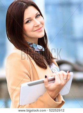 Businesswoman in coat working on digital tablet out of office overlooking cityscape