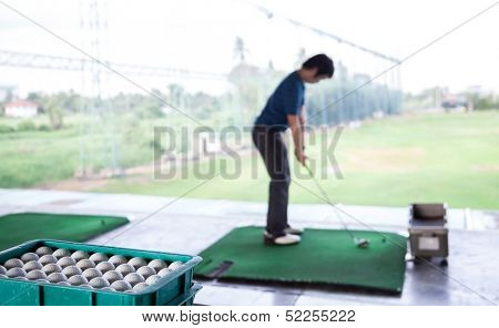 Young male golfer practicing his drive (Selective Focus at Golf ball tray)