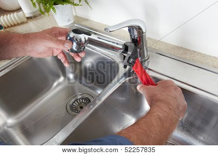 Hands of professional Plumber with a water tap and wrench.