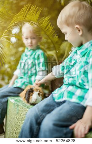 Image of twin boys posing with guinea pig