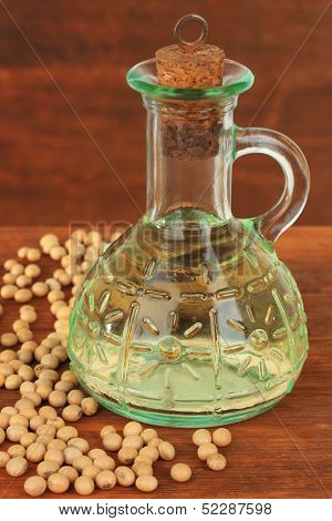 Soy beans and oil on wooden background
