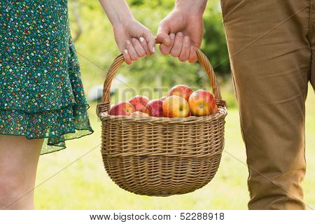 Basket of apples being carried by a young couple outside on sunny day