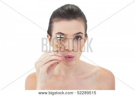 Pouting natural brown haired model using an eyelash curler on white background