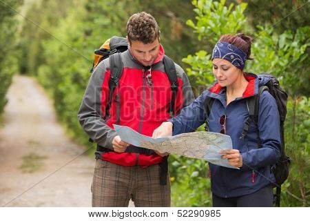 Happy couple going on a hike together looking at map in the countryside