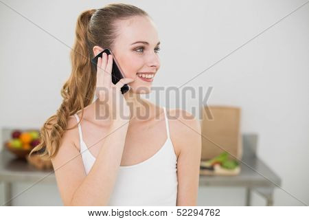 Smiling young woman talking on smartphone in the kitchen at home