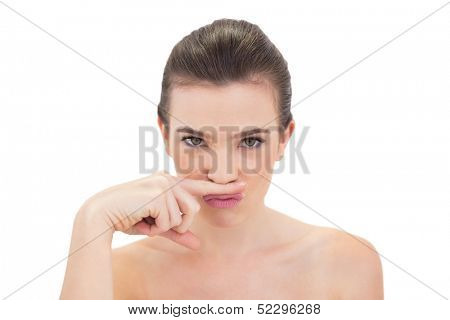 Pouting natural brown haired model putting her finger under her nose on white background