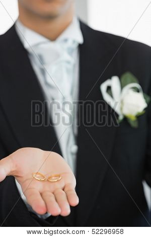 Young bridegroom showing wedding rings while wearing a suit