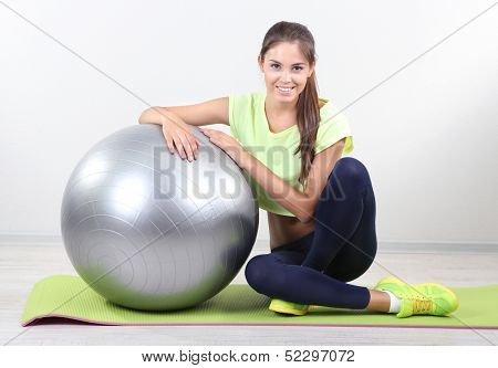 Beautiful young girl with grey ball at home