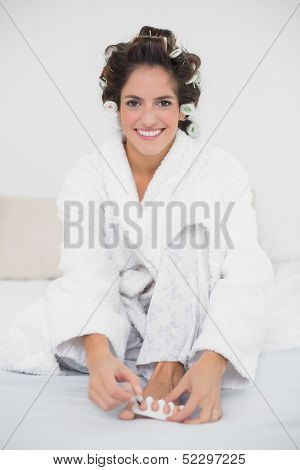 Smiling natural brunette applying nail polish to her toenails in bedroom