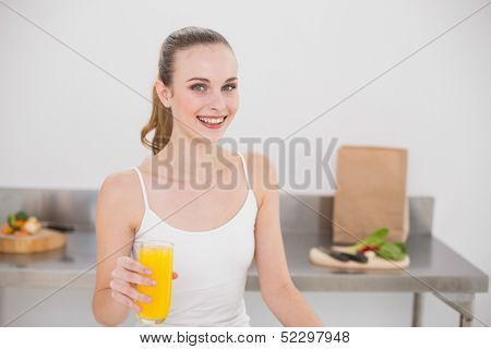 Cheerful young woman holding glass of orange juice in the kitchen at home
