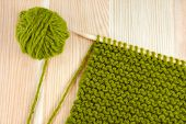 picture of garter  - Green ball of wool and garter stitch on a knitting needle on wooden table