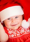 Closeup portrait of beautiful newborn baby wearing red Santa Claus hat, Christmas party, New Year ce