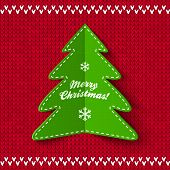 image of applique  - Green Christmas tree applique on red knitted background - JPG