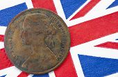 picture of copper coins  - One penny copper coin with an image of queen Victoria from 1864 on a British flag background - JPG