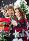 Portrait of young Caucasian couple with disposable cups and Christmas presents standing at store