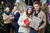 Portrait of happy young couple holding Christmas presents with parents standing in background at sto