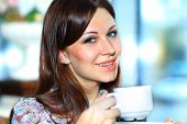 Portrait of attractive woman holding cup at cafe