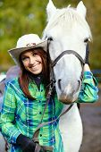 pic of cowgirl  - cute smiling cowgirl in a hat with a white horse - JPG