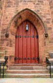 picture of entryway  - Imposing red door with black metal hardware in archway of brick church - JPG