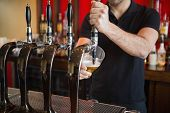 stock photo of pulling  - Barkeeper pulling a pint of beer behind the bar - JPG