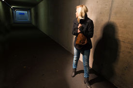 pic of underpass  - a young woman in an underpass for pedestrians is afraid of harassment and crime - JPG