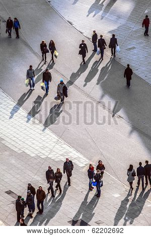 People Walking At The Street With Long Shadows